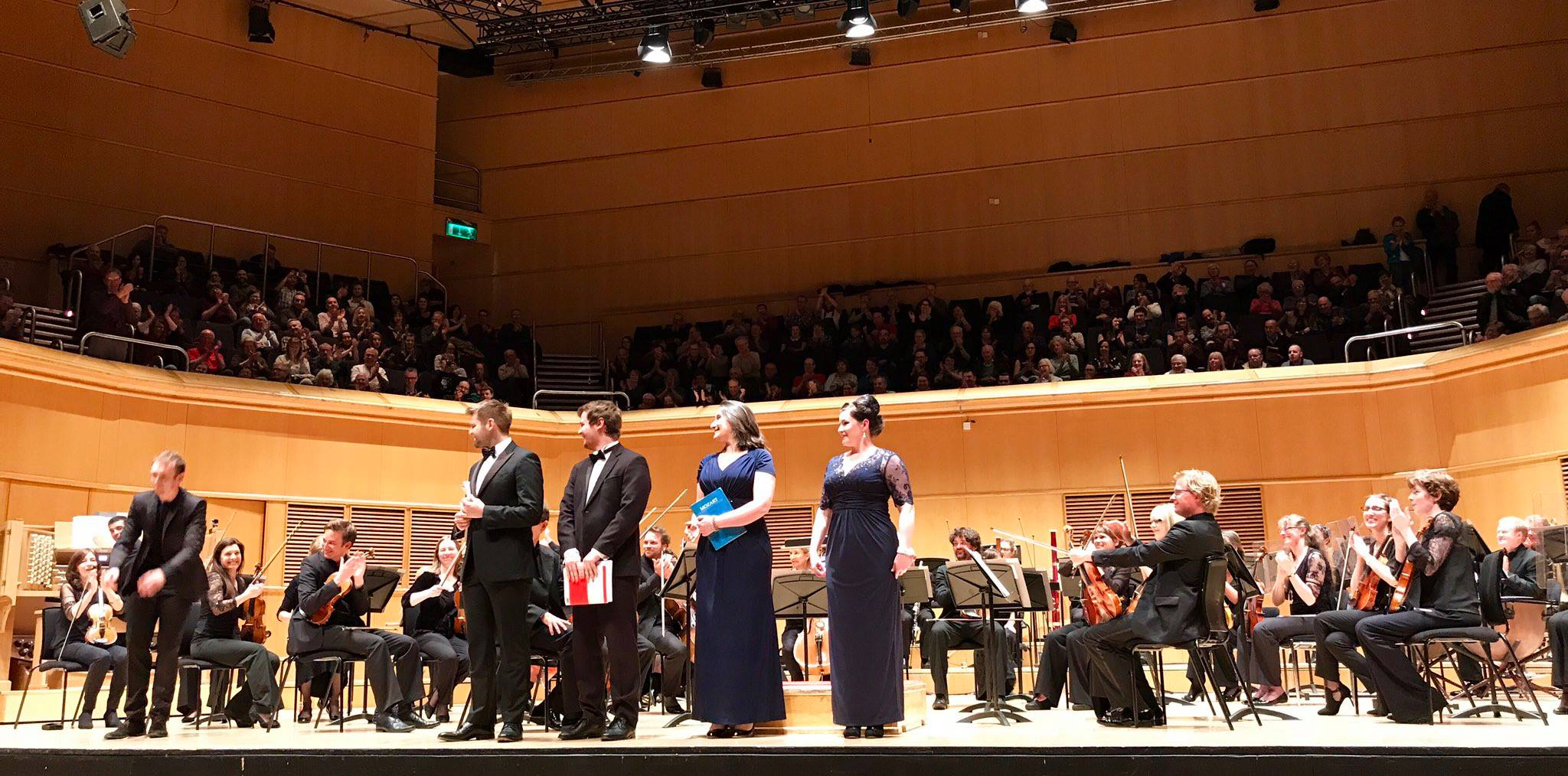 Colour photograph showing soloists on stage with the RSNO during a performance of the Mozart Requiem