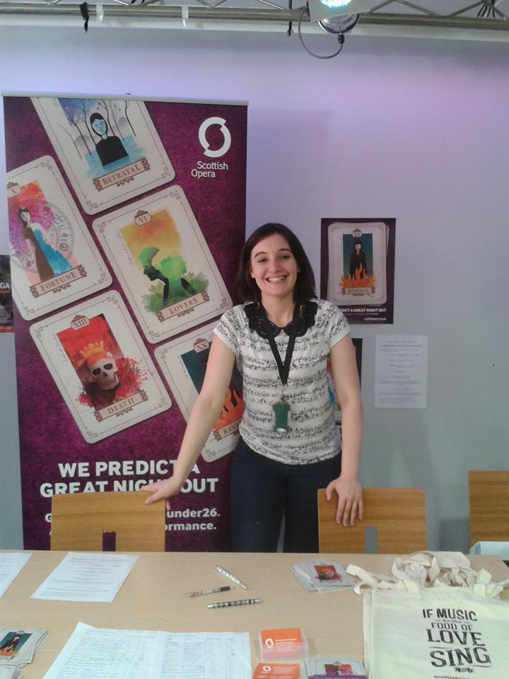 Colour photograph showing Beth Margaret Taylor on duty at an information desk in her role as Under-26 ambassador for Scottish Opera