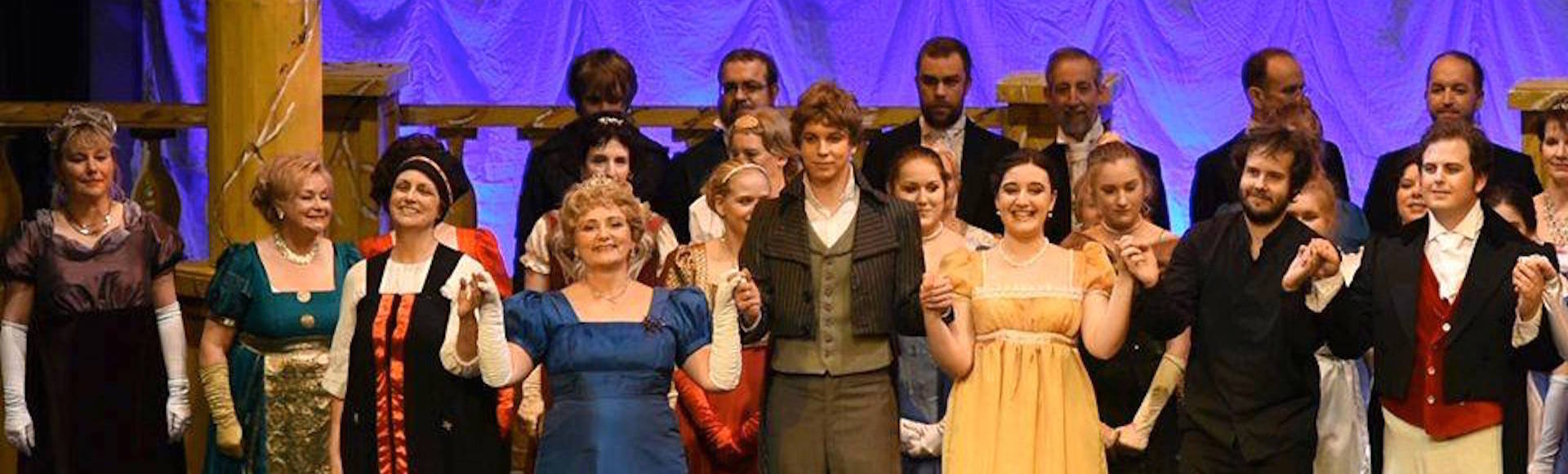 Colour photograph of the cast and conductor on stage at the end of a production of the opera, Eugene Onegin, by Fife Opera, (Courtesy of Doug Taylor on behalf of Fife Opera)
