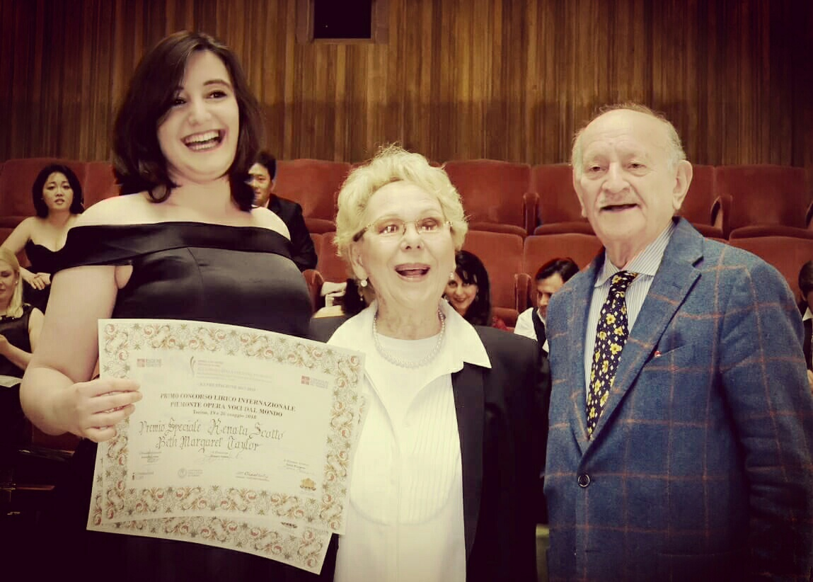 Colour photograph of Beth Margaret Taylor, mezzo soprano, together with Renata Scotto, soprano and president of the competition and jury, and Armando Caruso, president of the Accademia Della Voce Piemonte and vice-president of the competition, during the award ceremony at the 2018 Concorso Internazionale Piemonte Opera